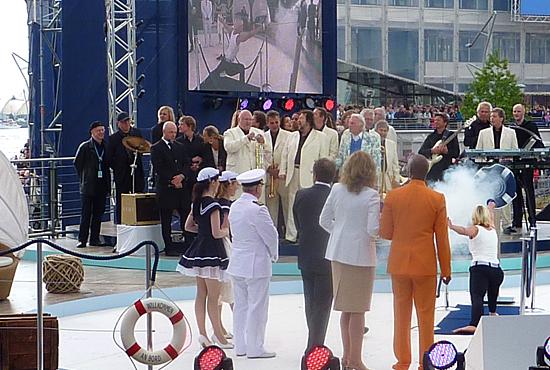 """Anja Fichtel, die Olympiasiegerin und mehrfache Medaillengewinnerin im Fechtsport, tauft die """"Mein Schiff 2"""" mit einem beherzten Fechtstoß auf die Zielscheibe, der die Flasche über ein Drahtseil gen Schiffswand in Bewegung setzt."""